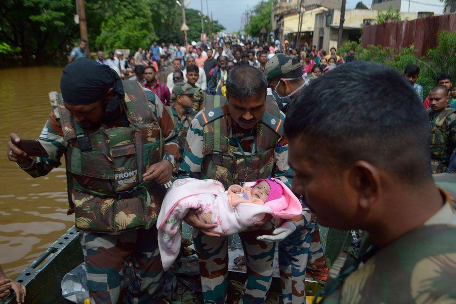 Un soldat indien tient un bébé dans ses bras, dans le district deSangli, dans l'Etat de Maharashtra.