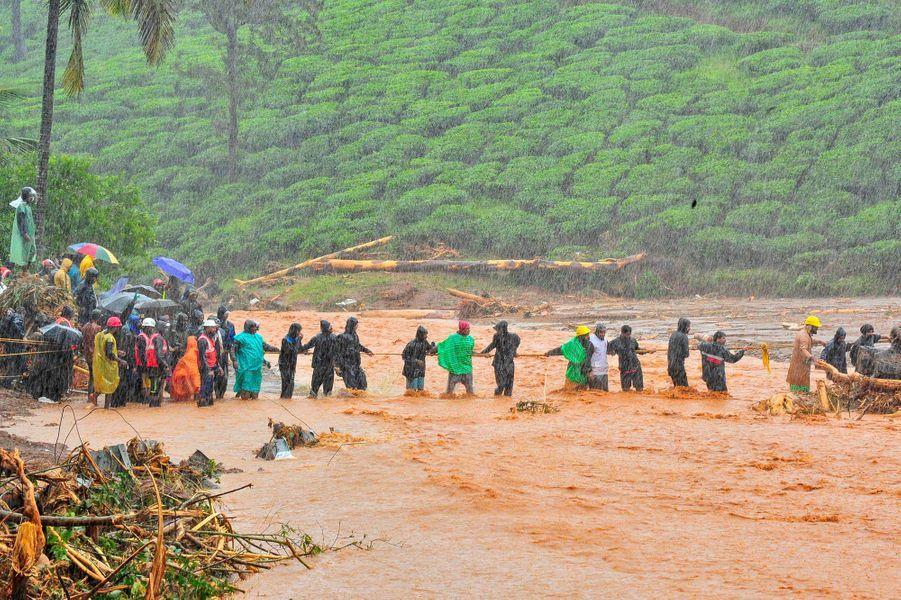 Une chaîne humaine pour tenter de traverser une rivière dans le district deWayanad, dans l'Etat du Kerala.