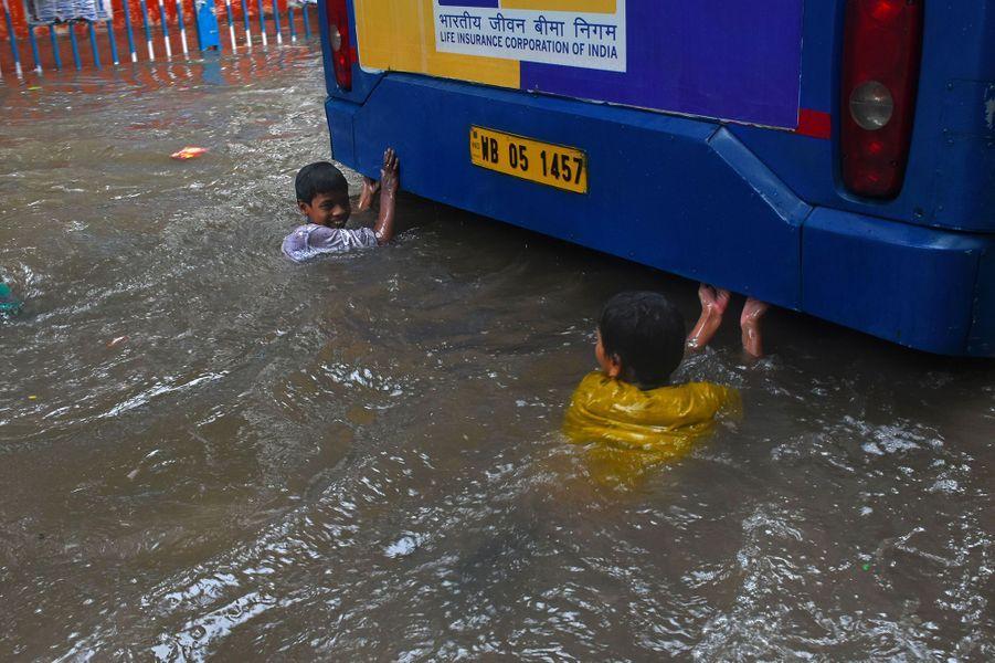 Deux jeunes nagent derrière un bus àKolkata.