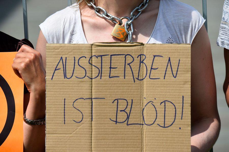 """Les manifestants, des jeunes du mouvement """"ExtinctionRebellion"""", se sont enchaînés au niveau du cou aux grilles de la chancellerie allemande pour dénoncer la politique insuffisante du gouvernement d'Angela Merkel face au changement climatique."""