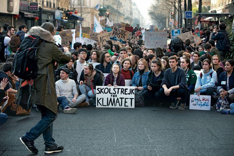 Avec sa pancarte « En grève pour le climat », Greta Thunberg en tête d'une manifestation de jeunes à Paris, le 22 février. De dos : son père.