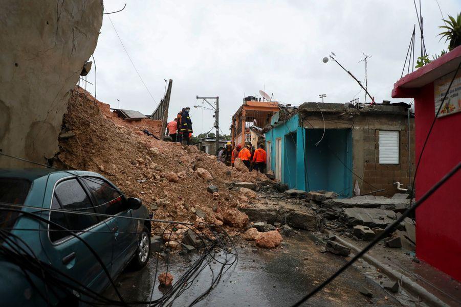 Des secouristes cherchent un mère et son enfant portés disparus sous les débris après la tempête.