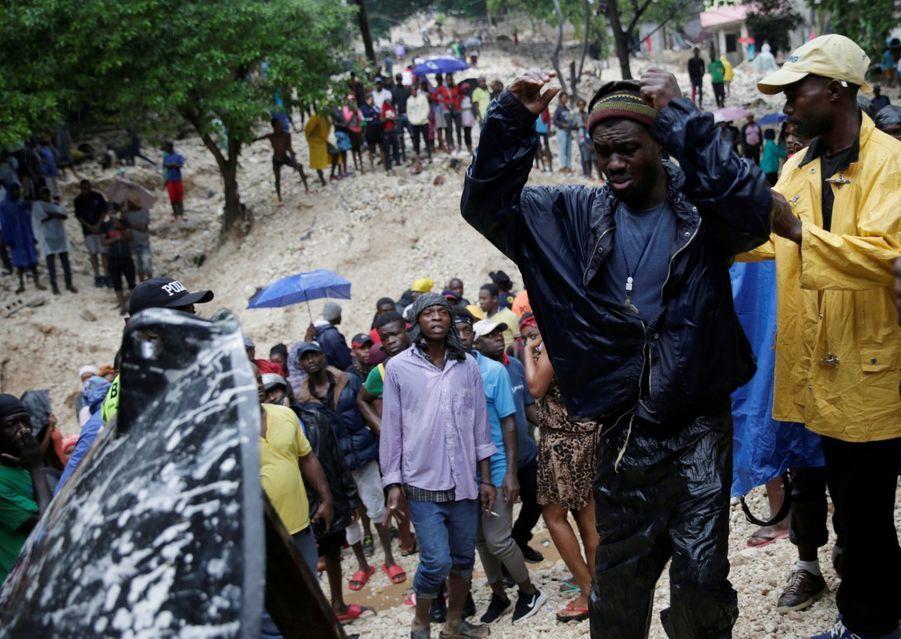 Un homme dévasté devant la corps sans vie de sa mère, tuée pendant la tempête à Port-au-Prince.