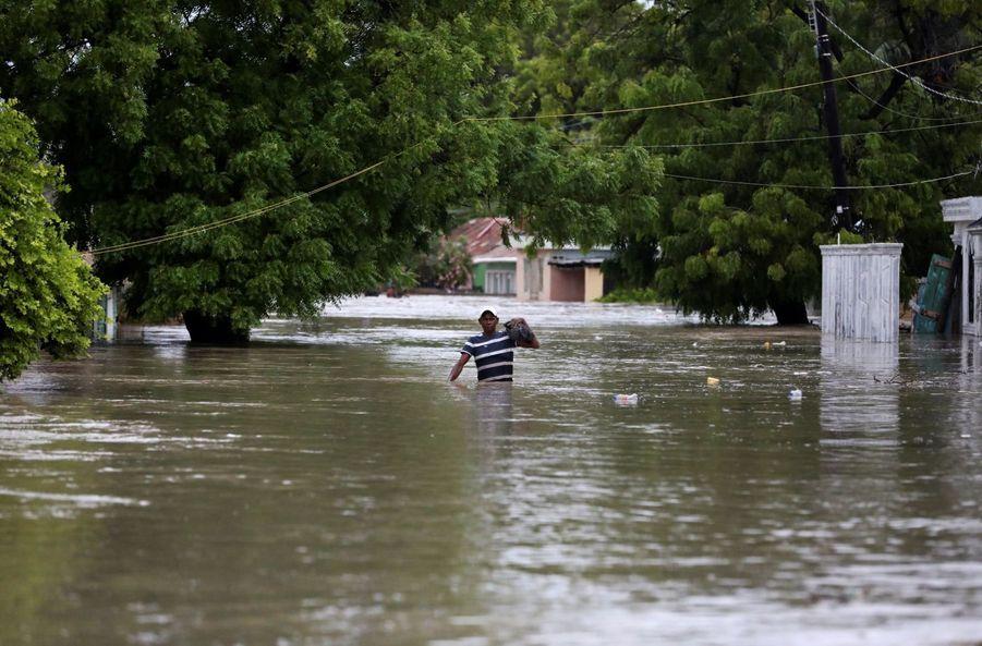 Un homme marche dans un rue inondée à Azua, en République dominicaine.