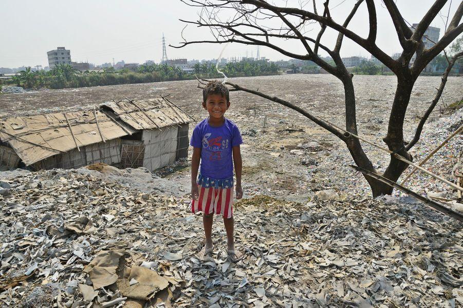 Un petit garçon devant une mer de déchets