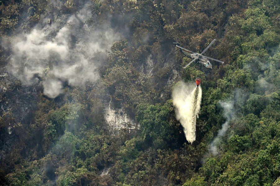 Un hélicoptère déverse de l'eau sur un incendie à Cali.