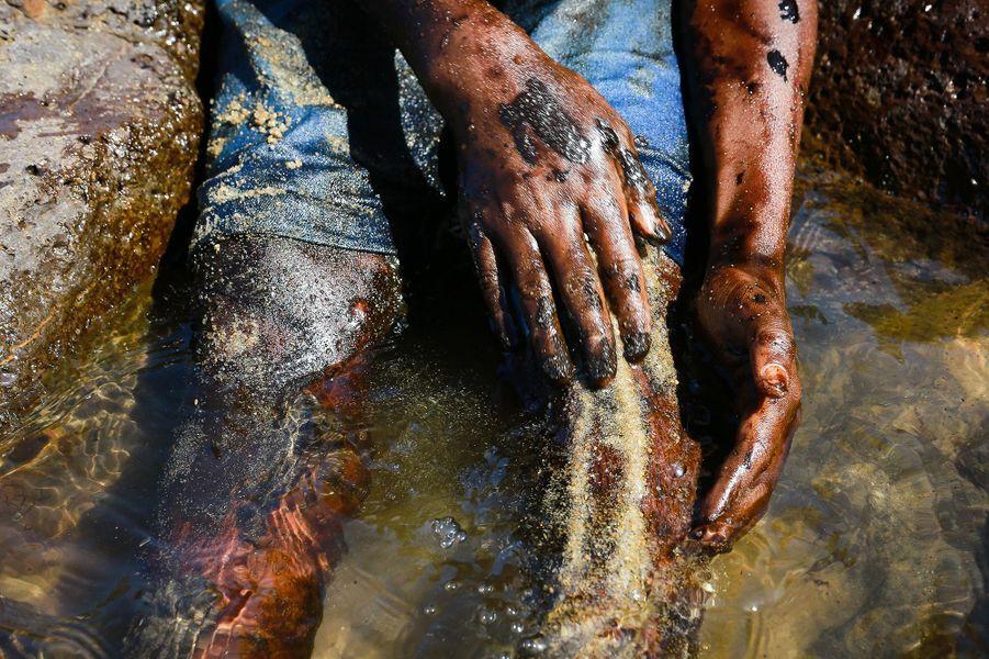 Everton Miguel dos Anjos, 13 ans, ainsi que des centaines de bénévoles, ont tenté de nettoyerla plage d'Itapuama, à Cabo de Santo Agostinho, dans l'Etat du Pernambouc, souillée par le pétrole.