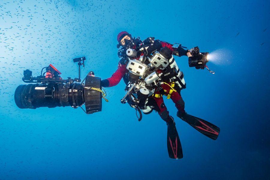 Thibault Rauby en sherpa sous-marin : appareils photo, rampe d'éclairage, propulseur, recycleur et bouteilles de secours.