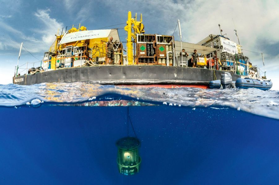 Sous l'eau, le petit ascenseur descend avec quatre plongeurs ; en surface, la barge avec son équipe de 30personnes.