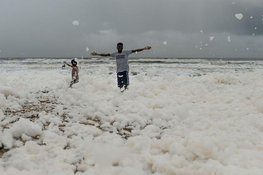 Malgré l'odeur âcre dégagée par la mousse provoquée par des agents polluants, des enfants jouaient à se rouler dedans et à se prendre en photo, sur les plages du Chennai, en Inde.