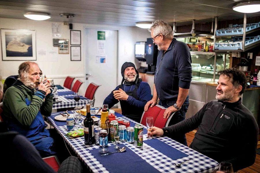 « Santé ! » Le capitaine du « Lance » (debout) vient trinquer avec Mike (bonnet), Borge (à g.) et l'un de leurs deux sauveteurs, Bengt Rotmo, le 8 décembre vers 2 heures du matin.