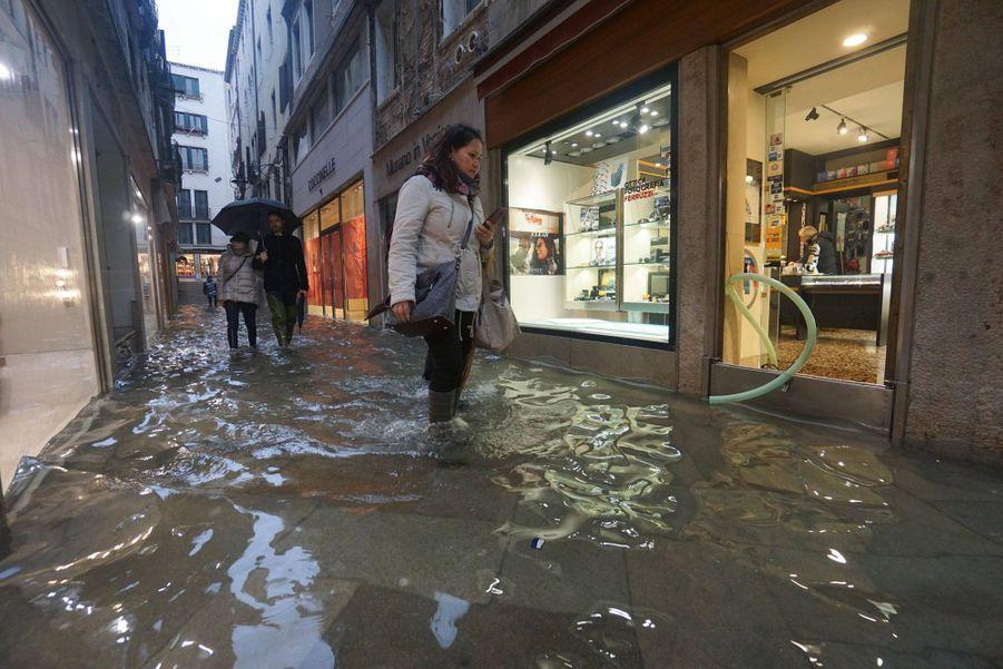 Dans une rue de Venise, dimanche. Les commerçants ont installé des obstacles pour empêcher l'eau d'envahir leurs boutiques.