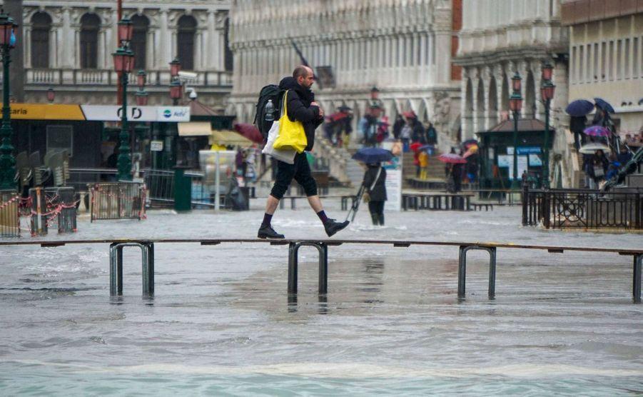 Un homme traverse sur une passerelle à Venise dimanche.