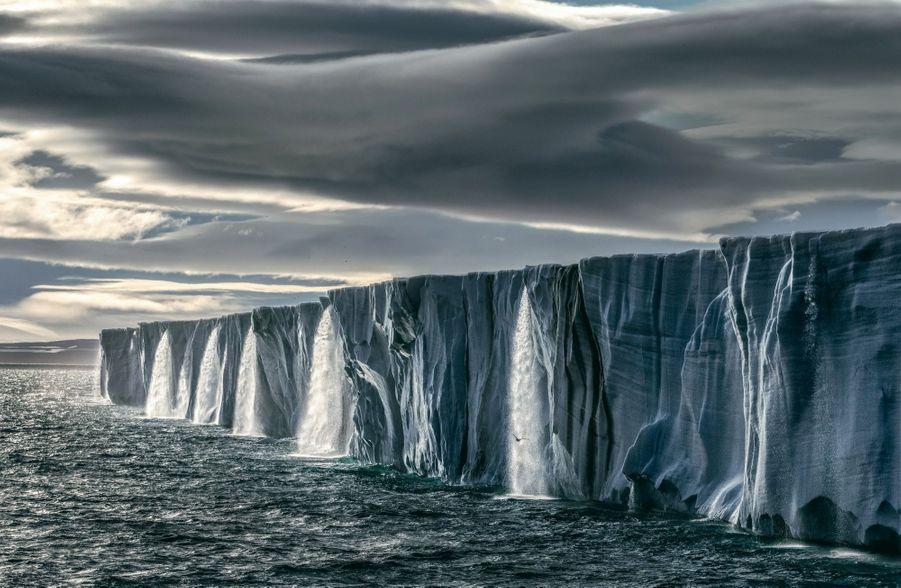 Fonte spectaculaire d'un glacier dans l'archipel norvégien du Spitzberg. En Arctique, il n'est plus rare d'enregistrer des températures de 25 °C supérieures aux normales saisonnières.Pour plus d'information sur la fondation SeaLegacy et la disponibilité des œuvres photographiques, contactez zoe@sealegacy.org