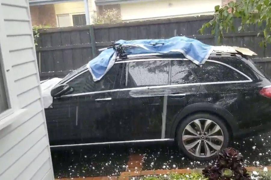 Pendant la tempête de grêle, un habitant tente de protéger son véhicule, àAshburton, Victoria.