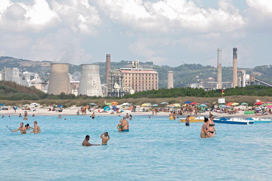 La plage blanche de Rosignano Solvay est connue pour sa couleur mais aussi son usinede produits chimiques Solvay, les pieds dans l'eau. Les flots bleus et le sable immaculé, c'est grâce à elle. Ou plutôt aux résidus de calcaire qui blanchissent tout.