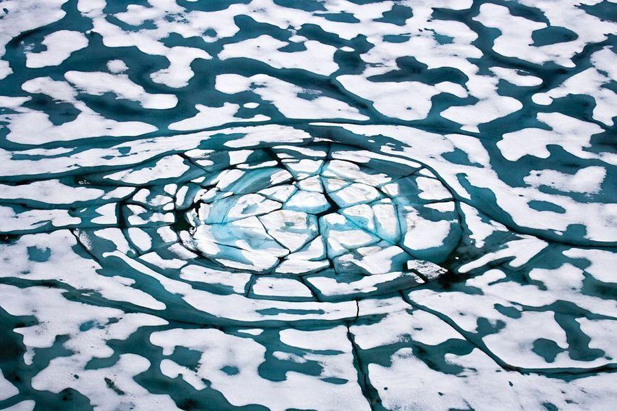 """Aujourd'hui, les calottes polaires fondent plus vite qu'elles ne se reconstituent. Le photographe franco-britannique, Sebastian Copeland s'est fait le témoin de leur fragilité au fil de lents périples : 8 000 kilomètres àski enArctiqueet enAntarctique. Il est, jusqu'au 15 novembre, à Paris Photo, au Grand Palais, pour la sortie de son dernier livre, « Arctica ». Un testament sur la beauté des grands déserts blancs. Et un cri d'alarme : « Ces trente dernières années, davantage de glace a disparu que pendant le million d'années précédent. »Dans ce monde hostile, les hommes et les bêtes avaient appris à vivre. Prudemment. Patiemment. Aujourd'hui, leur univers se disloque. Les phoques et les ours ne sont pas les seuls à pâtir d'une banquise évanescente. Quatre millions d'êtres humainspeuplent l'Arctique. Parmi eux, une myriade de peuples autochtones, au mode de vie intimement lié à cet environnement. Plus généralement, la santé des glaces et des neiges concerne l'équilibre de tout le monde vivant. En réverbérant les rayons solaires, elles jouent un rôle clé dans la régulation climatique.""""Je ne suis pas un écolo romantique qui veut sauver les ours polaires. La banquise, c'est de la géopolitique. J'incite, à ma façon, à la prise de conscience"""" assure Sebastian Copeland.A lire aussi: Sebastian Copeland face à la fonte des glaces - A l'Arctique de la mort"""