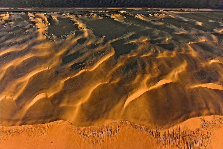 LA DUNE DU PILAT SE DONNE DES AIRS DE NAMIBIE 60 millions de mètres cubes de grains de quartz apportés par les vents et les courants du bassin d'Arcachon. Cette montagne de sable grandit à mesure que recule le trait de côte : chaque année, la plus grande dune d'Europe se déplace de 1 à 5 mètres.