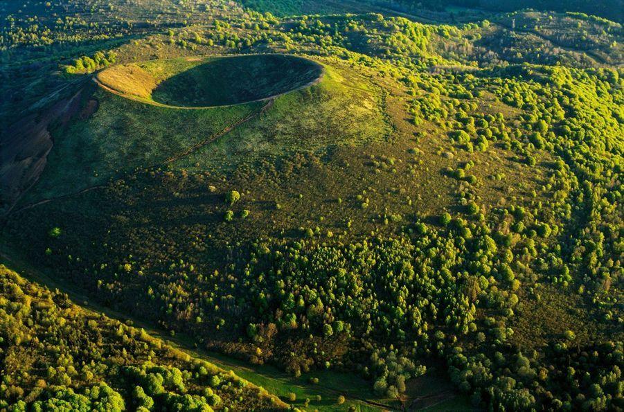 L'AUVERGNE, VERTE COMME LE RWANDA Culminant à 1 210 mètres, le Puy Pariou est l'un des 80 volcans de la chaîne des Puys. Accueillant autrefois un lac de lave, son double cratère forme un cercle parfait… et inoffensif : sa dernière éruption date de 6 250 avant J.-C