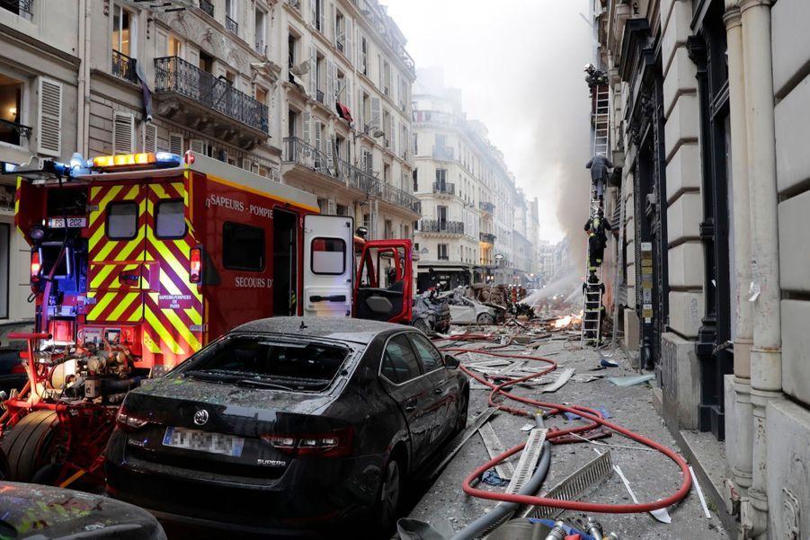 D'autres sortaient en robe de chambre ou finissaient de s'habiller précipitamment dans la rue en sortant des immeubles et hôtels voisins.