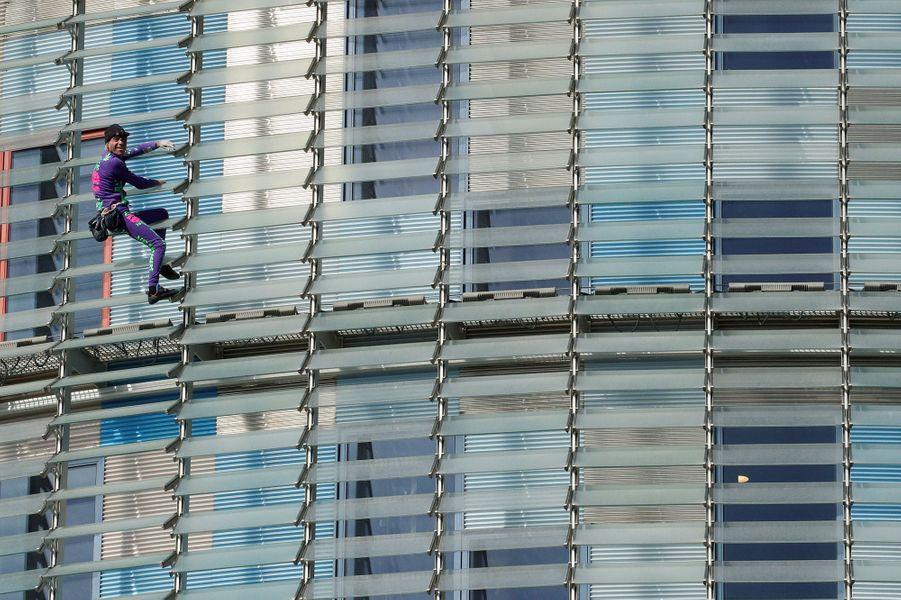 """Alain Robert, alias le «Spiderman français» a grimpé la Tour Agbar -145 mètres- de Barcelone sans corde ni assistance pour mettre en garde contre la """"peur"""" contagieuse autour du nouveau coronavirus."""