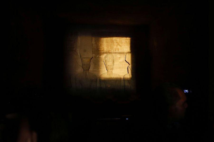 De nombreux visiteurs, dont des responsables égyptiens et un groupe d'ambassadeurs africains, ont observé la statue deRamsèsIIéclairée par le lever du soleil.