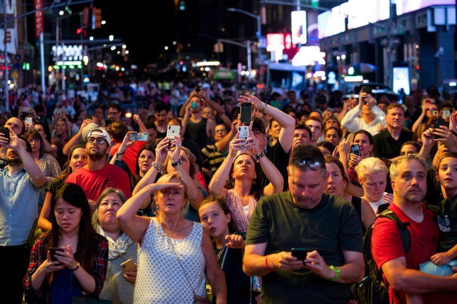 Les badauds, ébahis par le spectacle auquel ils assistent à Times Square.