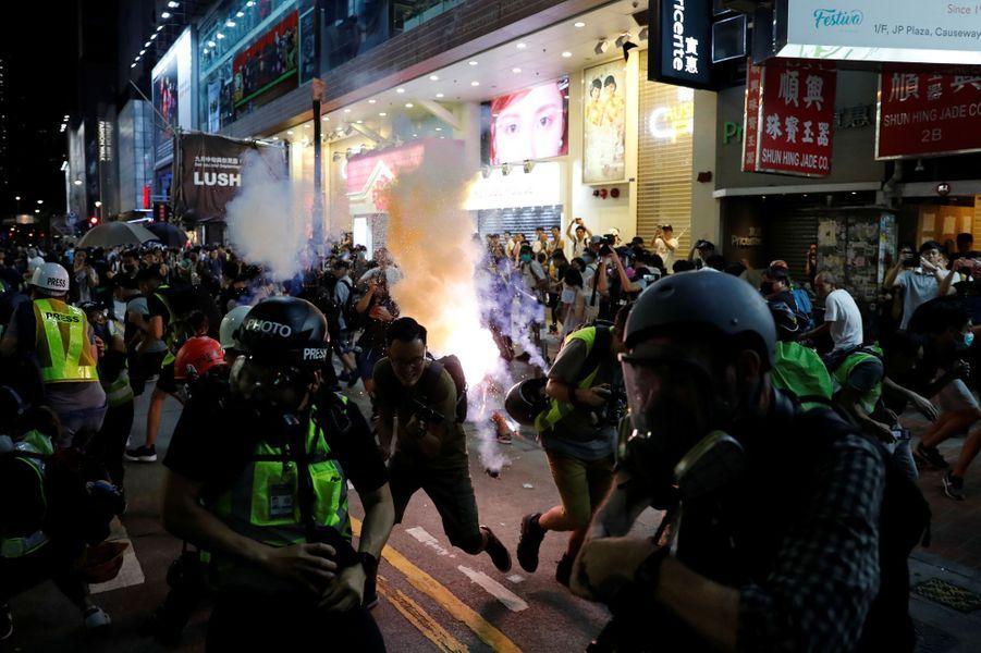 De nouvelles scènes de violence ont émaillé des manifestations interdites à Hong Kong dimanche soir, la police ayant recours aux lacrymogènes et canons à eau contre des militants pro-démocratie qui jetaient des pierres et des cocktails Molotov .
