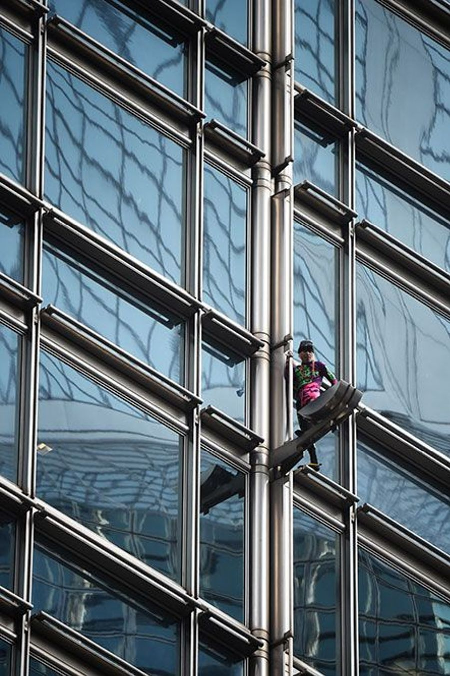 Alain Robert escalade leCheungKongCenter à Hong Kong, vendredi, pour y installer une banderole.