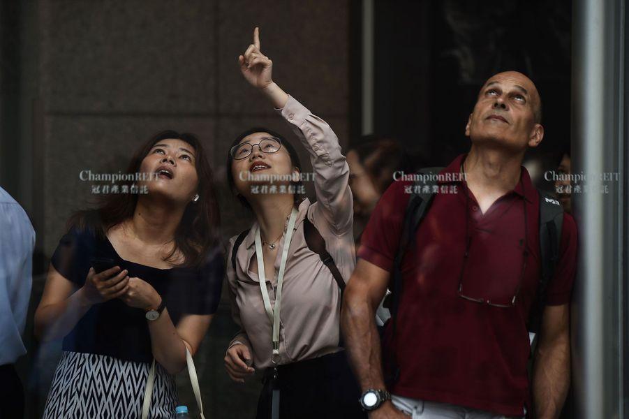 Des badauds admirent l'exploit d'Alain Robert à Hong Kong, vendredi.