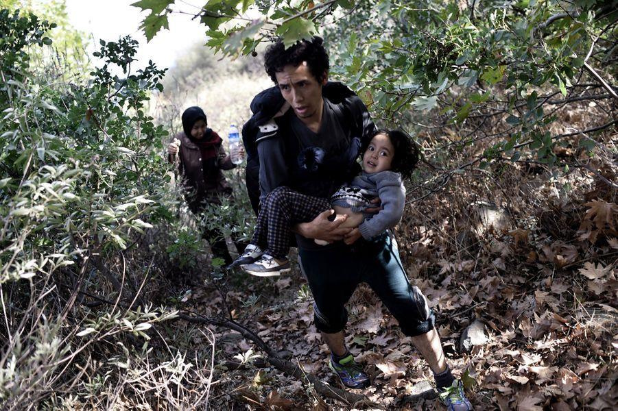 A peine débarqué, un réfugié porte son enfant exténué