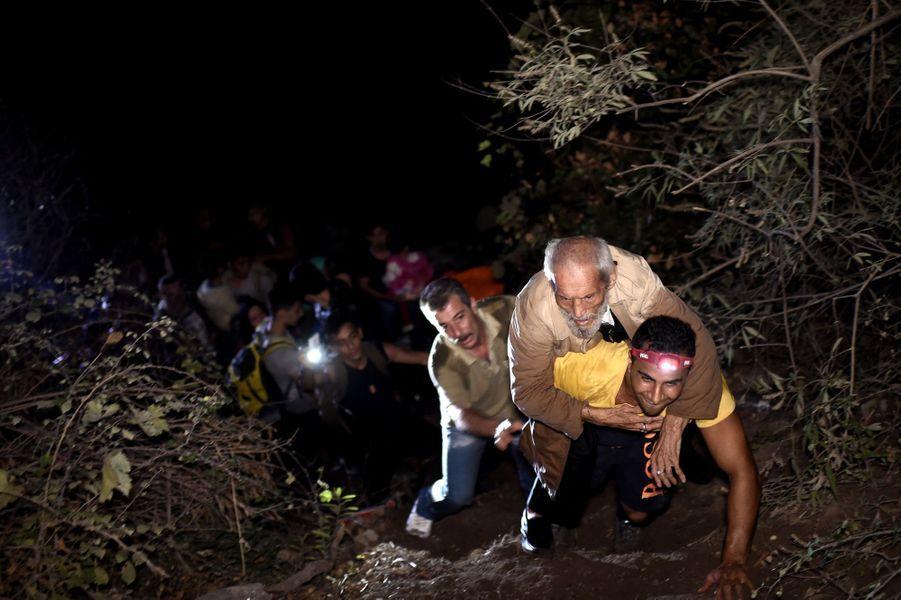 Le 26 septembre, un réfugié porte son dos un vieil homme trop faible pour marcher
