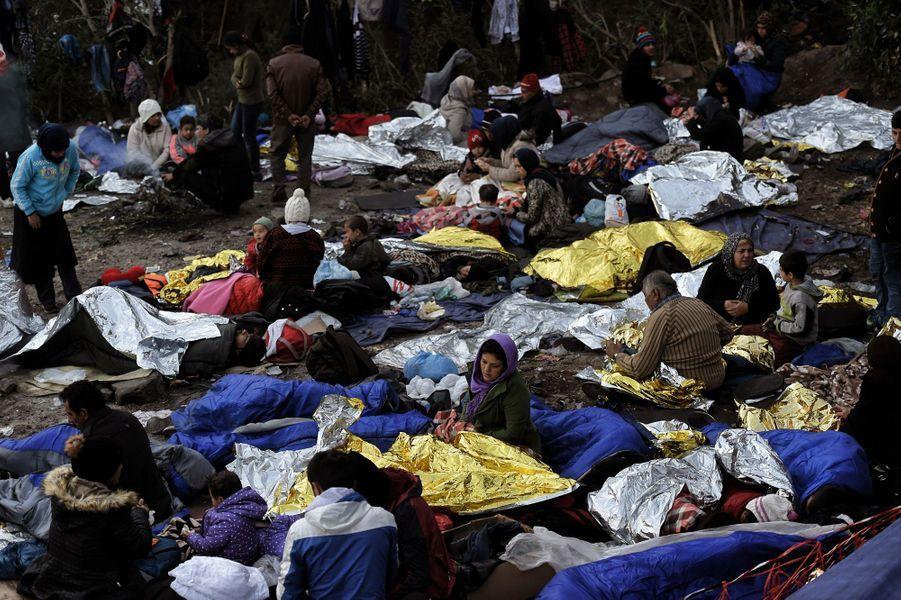 Saufs mais épuisés, des réfugiés s'enveloppent dans des couvertures de survie