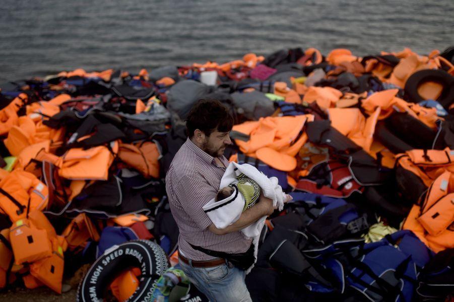 Un réfugié syrien porte son enfant devant un pile de gilets de sauvetage