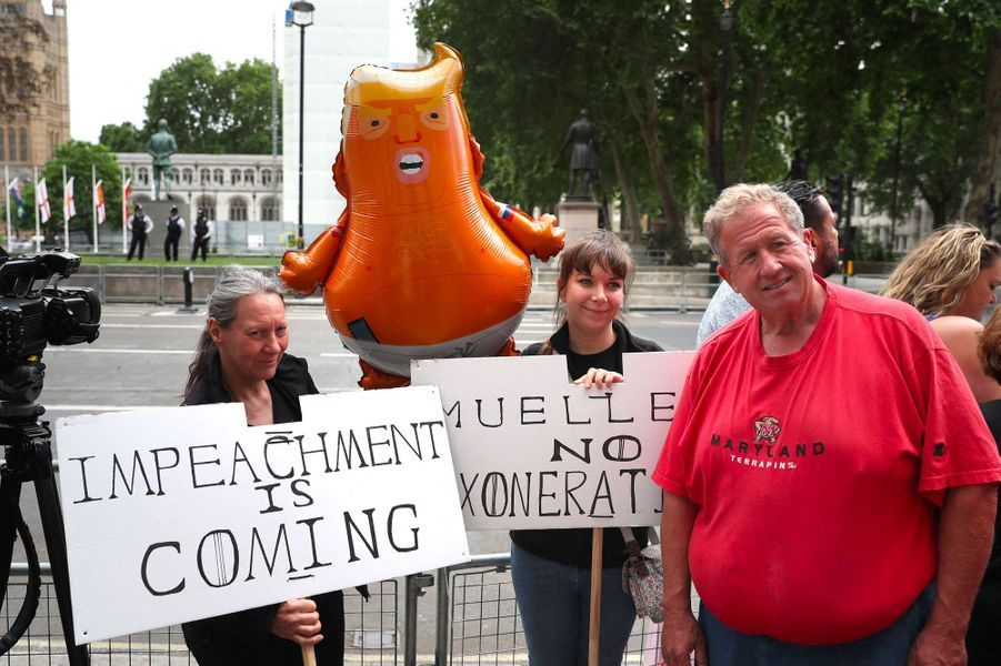 «La destitution approche», proclame la pancarte de gauche. Un ballon Trump, symbole de ralliement des anti-Trump britanniques, est également présent.