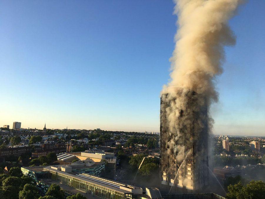 Plusieurs heures après le début de l'incendie, une énorme colonne de fumée s'échappait encore de la Grenfell Tower.