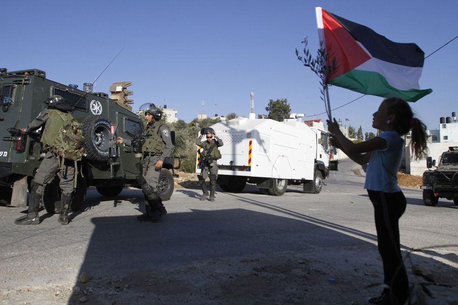 Ahed Tamimi brandit un drapeau devant un soldat.