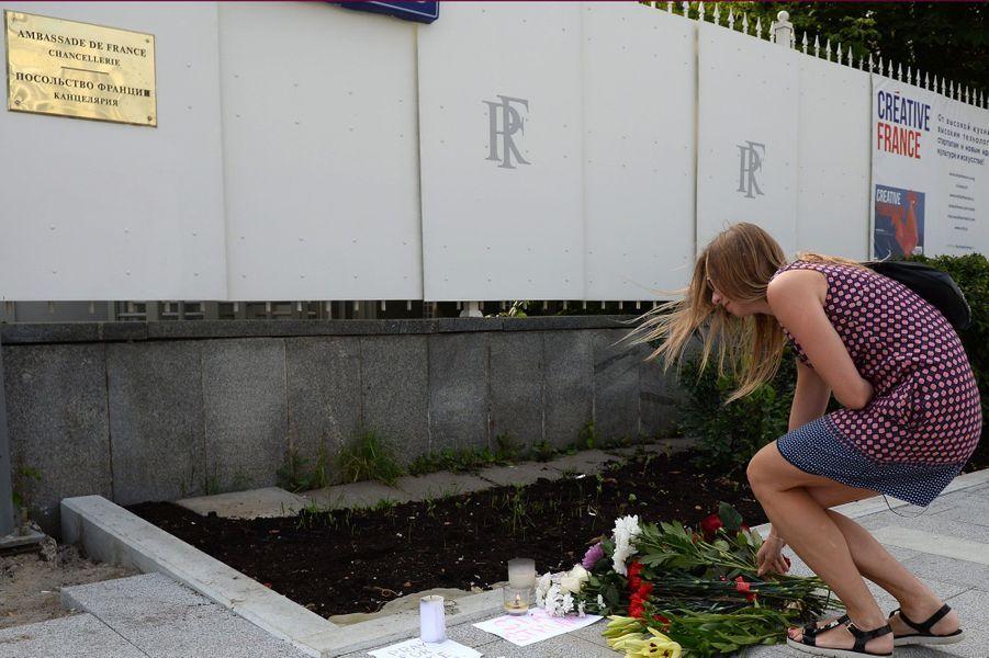 Une femme dépose des fleurs devant l'ambassade de France à Moscou