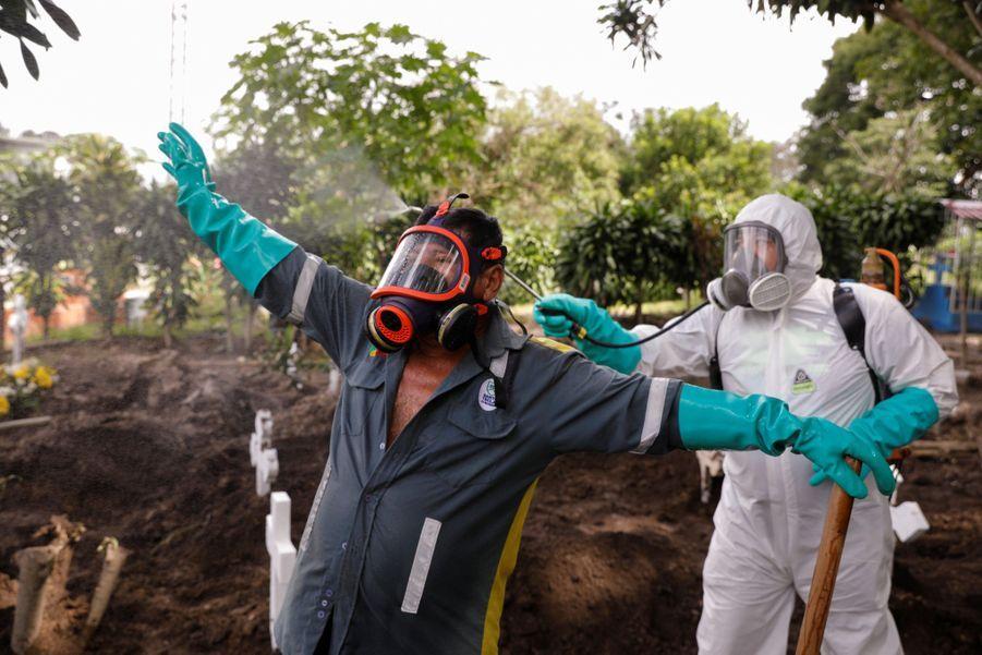 Un employé du cimetière est désinfecté après l'enterrement d'une femme atteinte du Covid-19.
