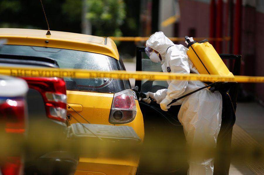 Un employé de nettoyage désinfecte un taxi dans lequel le passager vient de mourir du coronavirus.