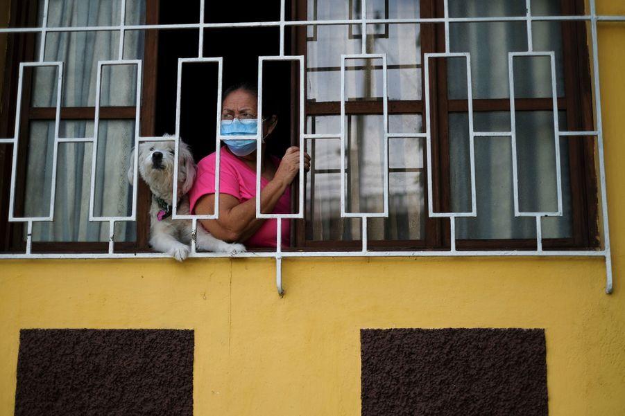 Leur travail est observé par une habitante àSoyapango, au Salvador.