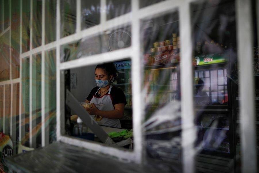 Une femme dans sa boutique à El Salvador, où le virus revient le plus fortement.