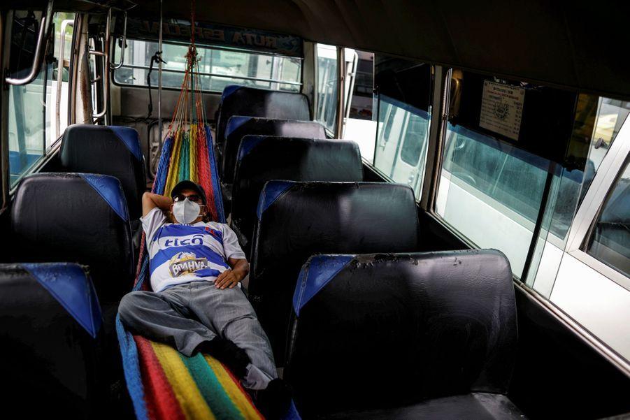 Le conducteur de ce car fait une sieste entre deux transports de soignants pendant l'épidémie de coronavirus au Salvador.