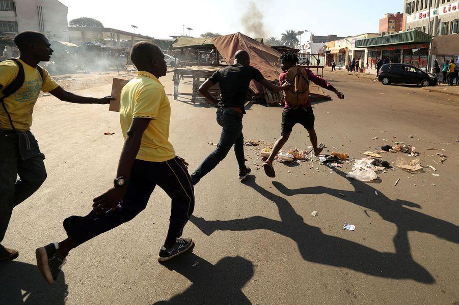 Des opposants poursuivent un homme qu'ils suspectent d'appartenir à la Zanu-PF, mercredi à Harare.