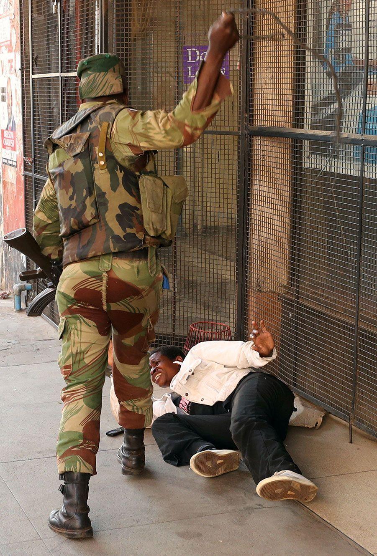 Un soldat frappe un homme à Harare, mercredi.