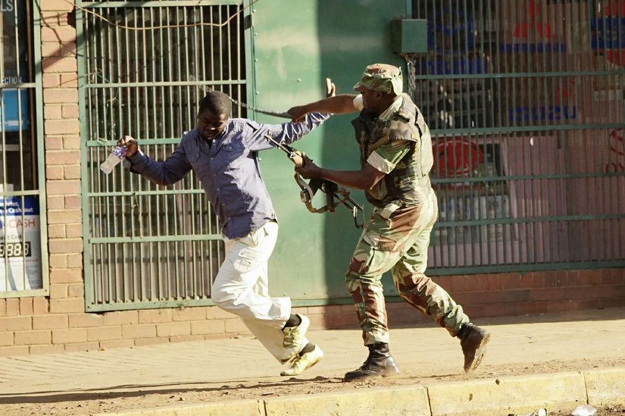 Un soldat frappe un homme dans la rue à Harare, mercredi.