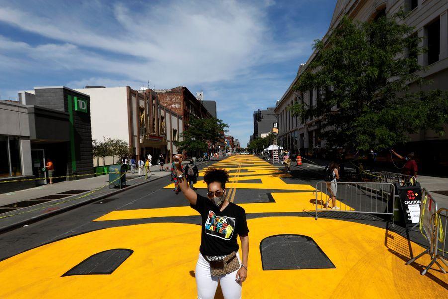 """Une femme pose devant le """"Black Live Matter"""" de Brooklyn."""