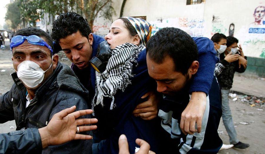 Une jeune femme évanouie est prise en charge par deux insurgés.