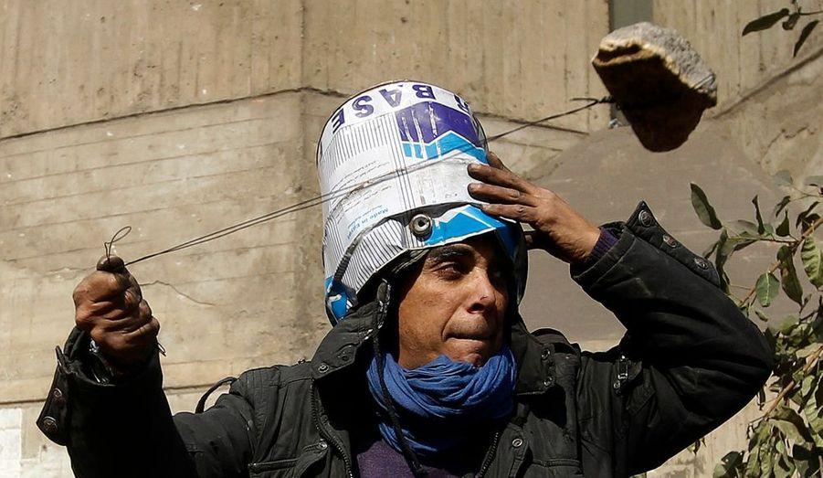 Un manifestant fait usage d'un lance-pierre contre les forces de l'ordre.