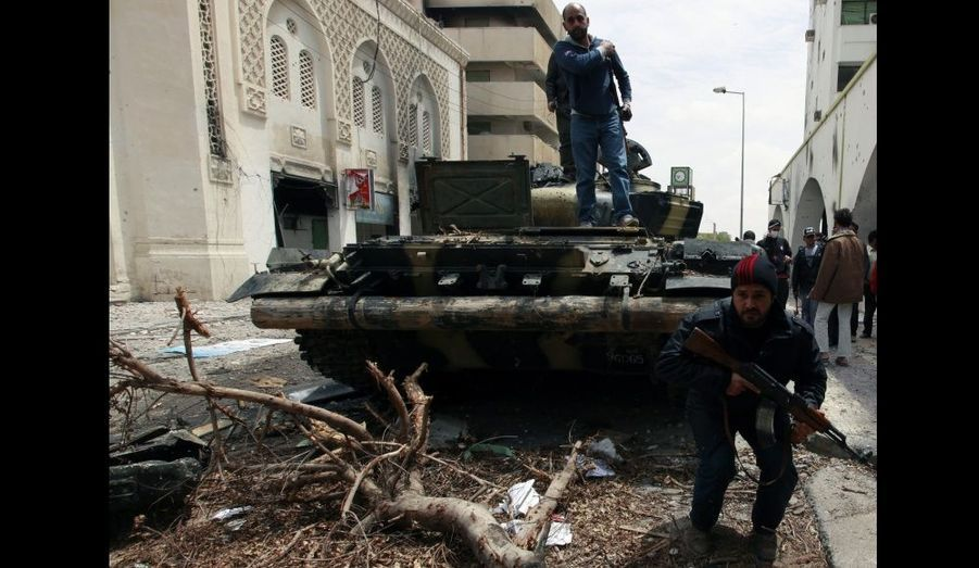 Un rebelle s'accroupit après d'un tank de l'armée, à Tripoli. Les forces libyennes pro-Kadhafi qui assiègent la cité portuaire de Misrata auraient reçu vendredi l'ordre de se retirer, rapporte Reuters.
